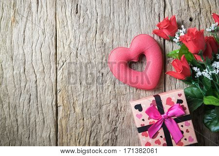 Red roses and gift box on a wooden background. Valentines Day Heart love background with hearts and flower. Valentines day red heart on old wood. Holidays card with copy space. Heart love background on wood. Heart love background and gift box. Heart love