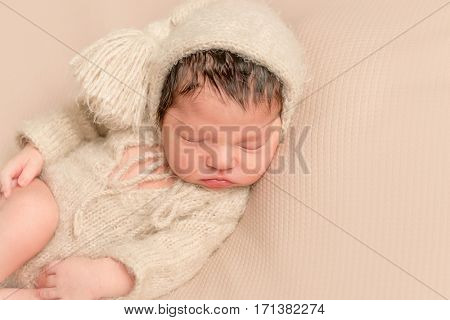 Adorable baby sleeping in a soft yellowish outfit, on a soft surface, on his side