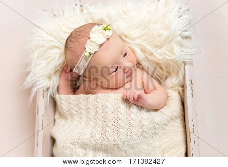 Adorable child wearing hairband laying in a baby basket with her eyes opened widely, closeup