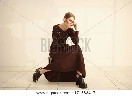 Young extravagant model sitting on chair near light wall