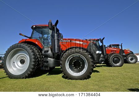 WEST FARGO, DAKOTA, September 13, 2016: Huge red Magnum 200, 270, and 280 tractors parked at the Big Iron display show in West Fargo, ND are  products of Case IH which offers agricultural equipment, financial services, as well as parts and service support