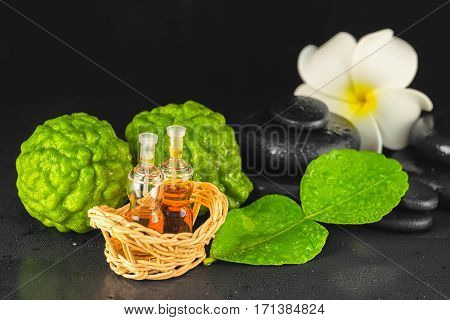 Spa Concept Of Bergamot, Leaf, Fragrance Oil, White Plumeria And Zen Basalt Stones With Water Dew On