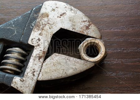 Ruusty Adjustable Wrench and Nut. Wooden Surface.