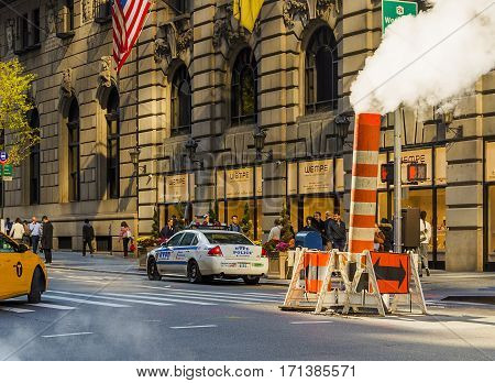 New York, USA, november 2016: Manhattan street scene with steam coming from manhole cover