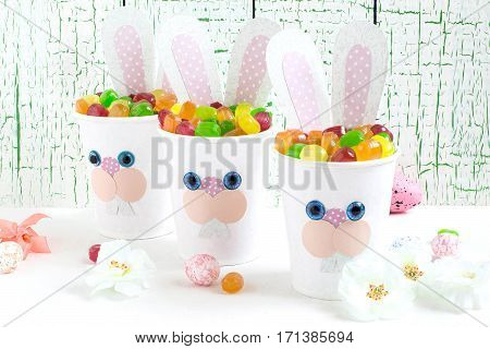 Paper cups in the form of funny Easter Bunny with candy. Homemade applique on paper cups. The idea for children gifts. DIY concept for the celebration of Easter