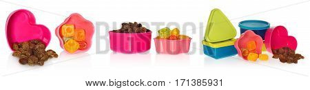 Multi colored kitchen molds with raisins and candy. Box closed in the shape of heart,  star, asquare and a circle. Containers in the colors blue, dark blue, yellow, pink, red.  cookie cutters on a white background with slight reflection.