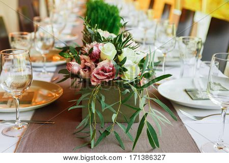 Beautifully organized event - served festive table ready for guests, decorated with flowers. Event in restaurant outdoors. Banquet, wedding decor, celebration.