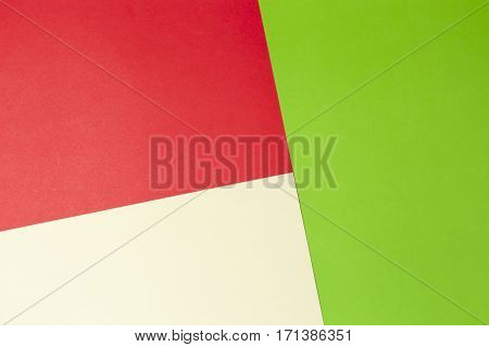 Greenery, red and yellow colored paper background. Copy space for text or image