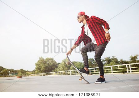 Picture of young dark skinned man wearing sunglasses skateboarding. Against the nature background.