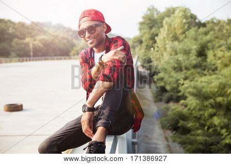 Picture of attractive dark skinned man wearing sunglasses. Sitting against nature background.