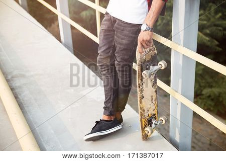 Cropped poung dark skinned man holding skateboard. Against the nature background.