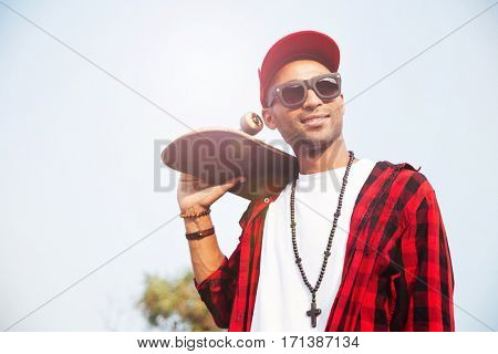 Picture of attractive dark skinned man wearing sunglasses and cap holding skateboard. Against the nature background.