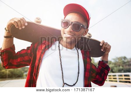 Photo of young dark skinned man wearing sunglasses holding skateboard. Against the nature background.