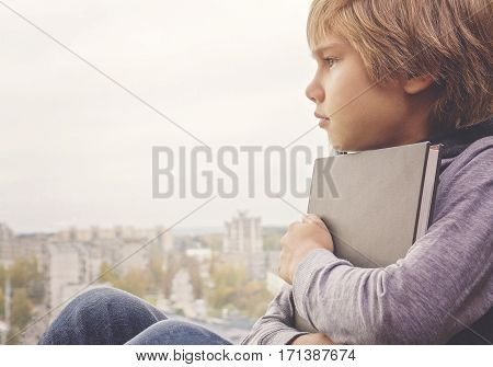 Young thoughtful dreaming boy with book sitting and looking through the window