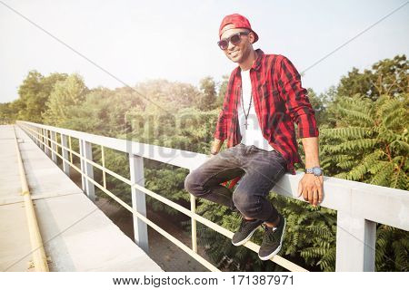 Picture of happy dark skinned guy wearing sunglasses sitting against nature background