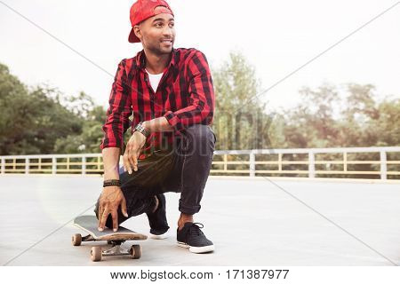 Picture of happy dark skinned young guy wearing cap sitting near his skateboard. Against nature background.