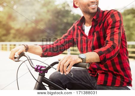 Cropped picture of happy dark skinned guy wearing cap sitting on his bicycle. Against nature background.