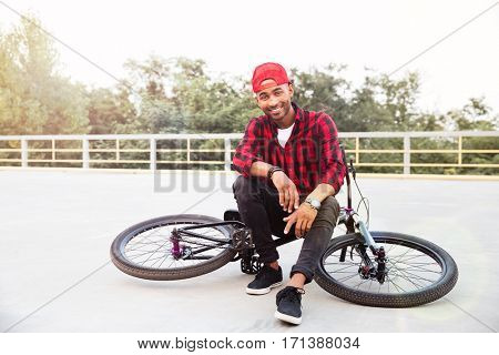 Photo of attractive dark skinned boy wearing cap sitting on his bicycle. Against nature background. Looking at the camera.