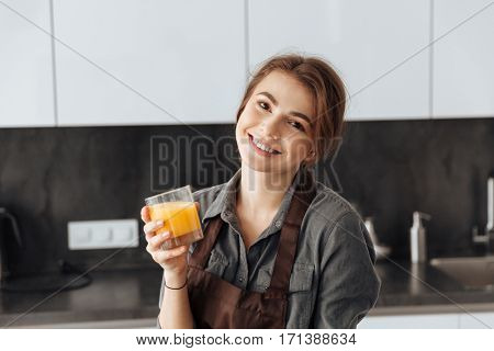 Image of young cheerful woman standing in kitchen holding glass of juice in hands.