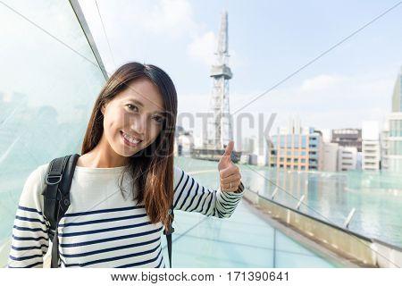 Woman showing thumb up in Nagoya city of Japan