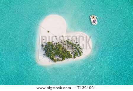 Beautiful small tropical island in heart shape, catamaran boat anchoring.