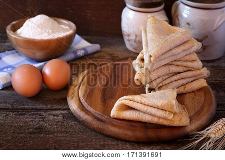 Pancakes and ingredients on wooden background, rustic style