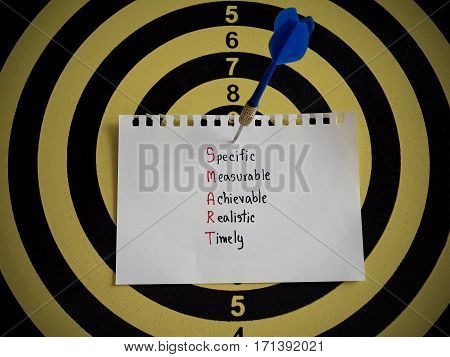 Handwriting SMART Goal on notepaper with dart arrow and dart board. (Selective focus)
