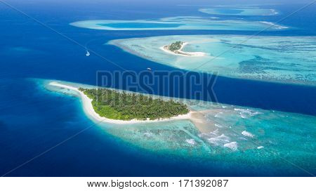 Small tropical island in Maldives atoll from aerial view