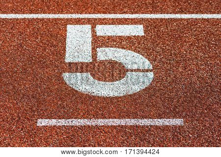 Start number five at cinder track of track and field running track