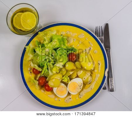 top view of a salad with potatoes cherry tomatoes and eggs chipped on a yellow plate drink water with lemon vegetarian dish