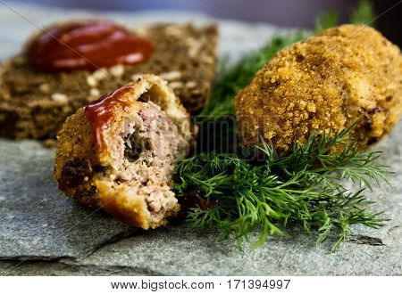 Homemade meat cutlets with parsley, ketchup and bread on white plate.