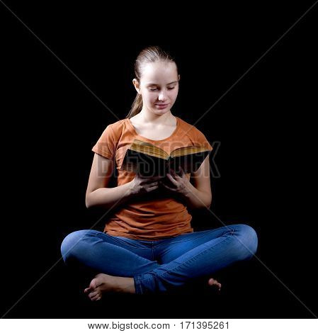 Teenage girl sitting and reading book on black background