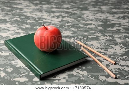 Apple, textbook and pencils on camouflage background
