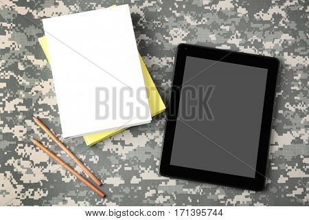 Tablet and copybooks on camouflage background