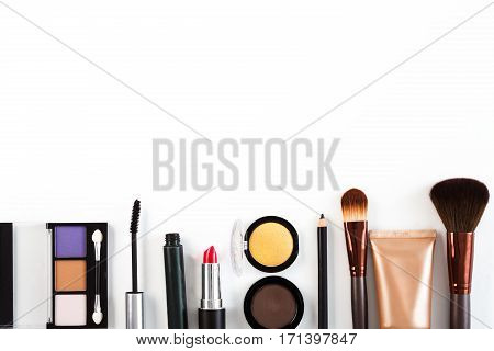 Makeup cosmetics, brushes and other essentials border on white background. Top view, flat lay with copy space. Beauty tools collection, lipstick, eyeshadow, mascara, foundation and more