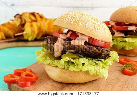Burgers with liver cutlet tomatoes pickles lettuce spicy sauce and a soft bun with sesame seeds on a cutting board and potato slices on skewers. Close up