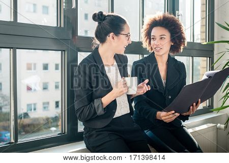 Two young female colleagues reviewing business reports during break in the office