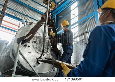 Low-angle view of two workers handling equipment for lifting industrial steam boilers