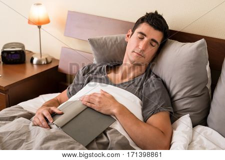 Young man falling asleep while reading a book in bed at home