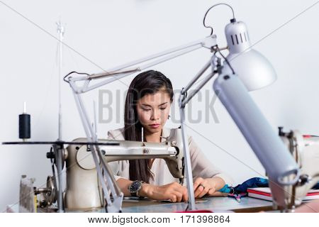 Woman using sewing machine, addition of buttons, red fabric, fixing pins