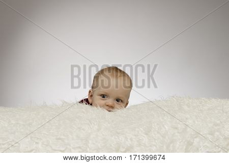 Kid looking from behind a white blanket on a gray background. Studio shot