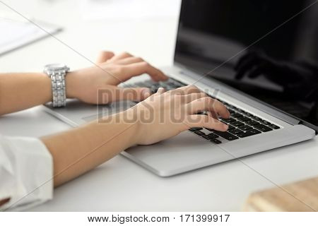Young woman working with laptop in office, closeup