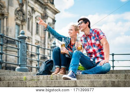 tourists, woman and man, enjoying the view from bridge at the Museum Island in Berlin with beer