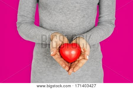 Gentle girl holding a res heart