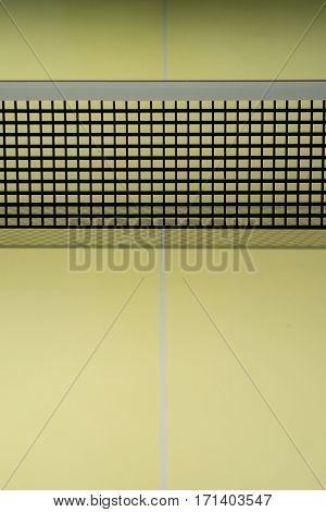 the black table tennis nets on the yellow table tennis table
