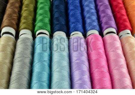Closeup sewing threads multicolored background in a paper roll