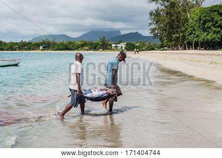 Tamarin Mauritius - December 9 2015: Fishermen carry two tuna on the beach of Tamarin Bay in Mauritius.