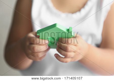Child holding figure in shape of house, closeup. Adoption concept