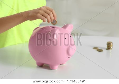 Little girl with piggy bank sitting at table, closeup