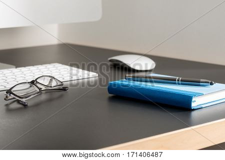Pen On Notebook And Eyeglasses By A Computer On Office Table
